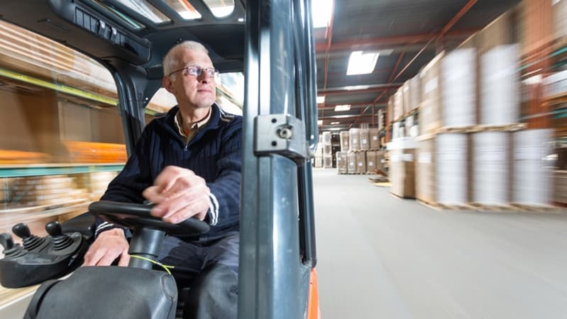 Old fella drives electric forklift.