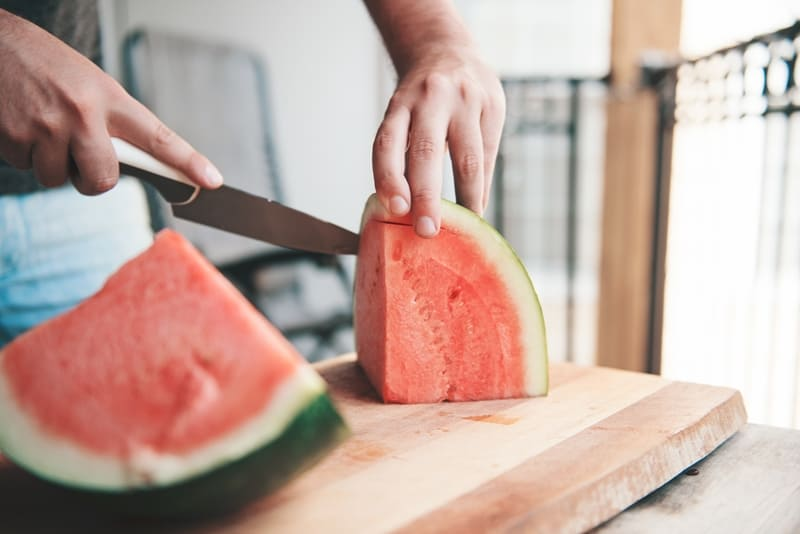 Man cutting watermelon.